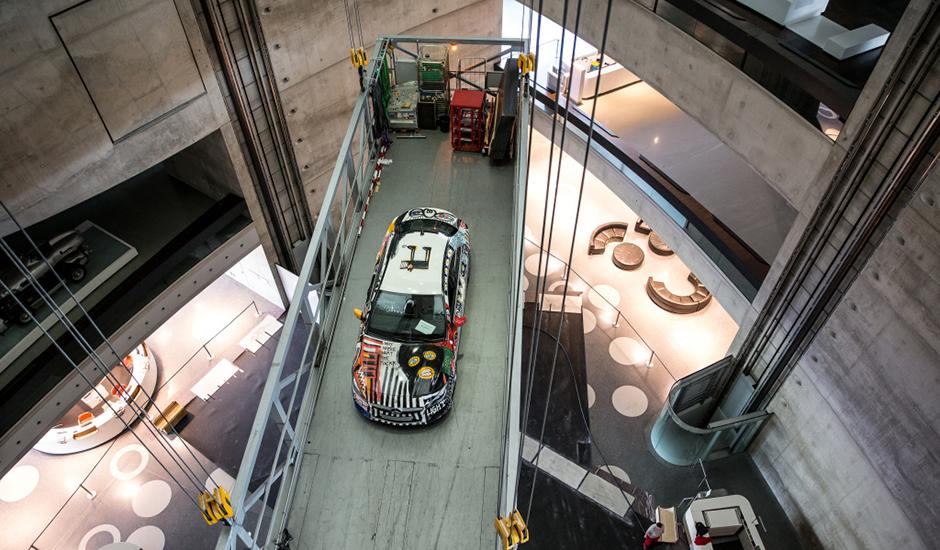 """Fahrzeugeinbringung im Mercedes-Benz Museum: Der Mercedes-Benz CLA StreetStyle designed by Cro auf dem Weg in den Raum Collection 4 """"Galerie der Namen"""". CLA StreetStyle designed by Cro is lifted up into Collections Room 4."""