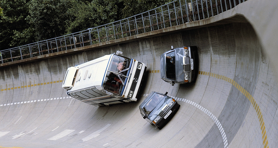 In der Steilkurve der Einfahrbahn des Werks Untertürkheim: Mercedes-Benz Limousine der Baureihe 201, S-Klasse-Limousine der Baureihe 126 und ein O 303 Reise-Omnibus, 1984. In the steep-bank curve of the test track at the Untertürkheim plant: a Mercedes-Benz Saloon from the 201 model series, an S-Class Saloon from the 126 model series and an O 303 touring coach, 1984.