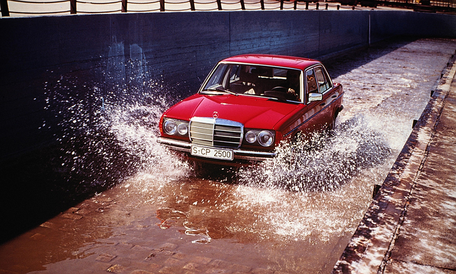 Mercedes-Benz Limousine der Baureihe 123, Wasserdurchfahrt auf der Einfahrbahn im Werk Untertürkheim. A Mercedes-Benz 123-series Saloon drives through a water basin on the test track at the Untertürkheim plant.
