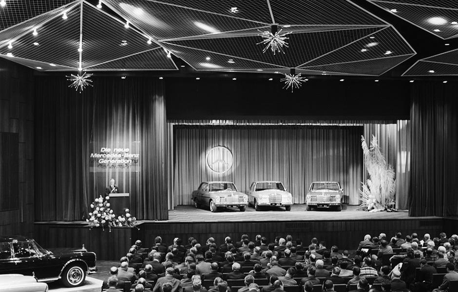 """Präsentation der """"Neuen Mercedes-Benz Generation"""" am 9. und 10. Januar 1968 in Sindelfingen. Chefingenieur Hans Scherenberg (links) stellt die neuen Typen (auf der Bühne, von links nach rechts) 220 D (W 115), 280 S (W 108) und 250 (W 114) vor. Presentation of the """"New Mercedes-Benz Generation"""" on 9 and 10 January 1968 in Sindelfingen. Head Engineer Hans Scherenberg (left) presents the new models (on the stage, from left to right) 220 D (W 115), 280 S (W 108) and 250 (W 114)."""